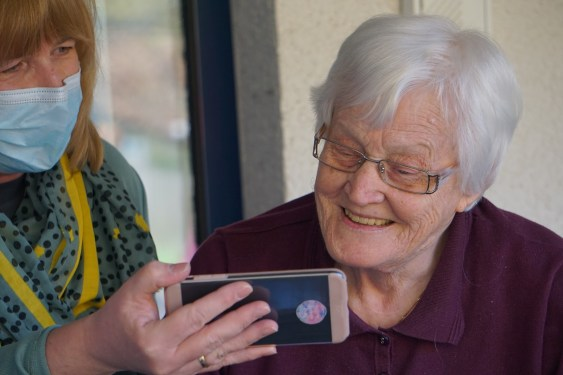 Caregiver showing phone to an elderly woman
