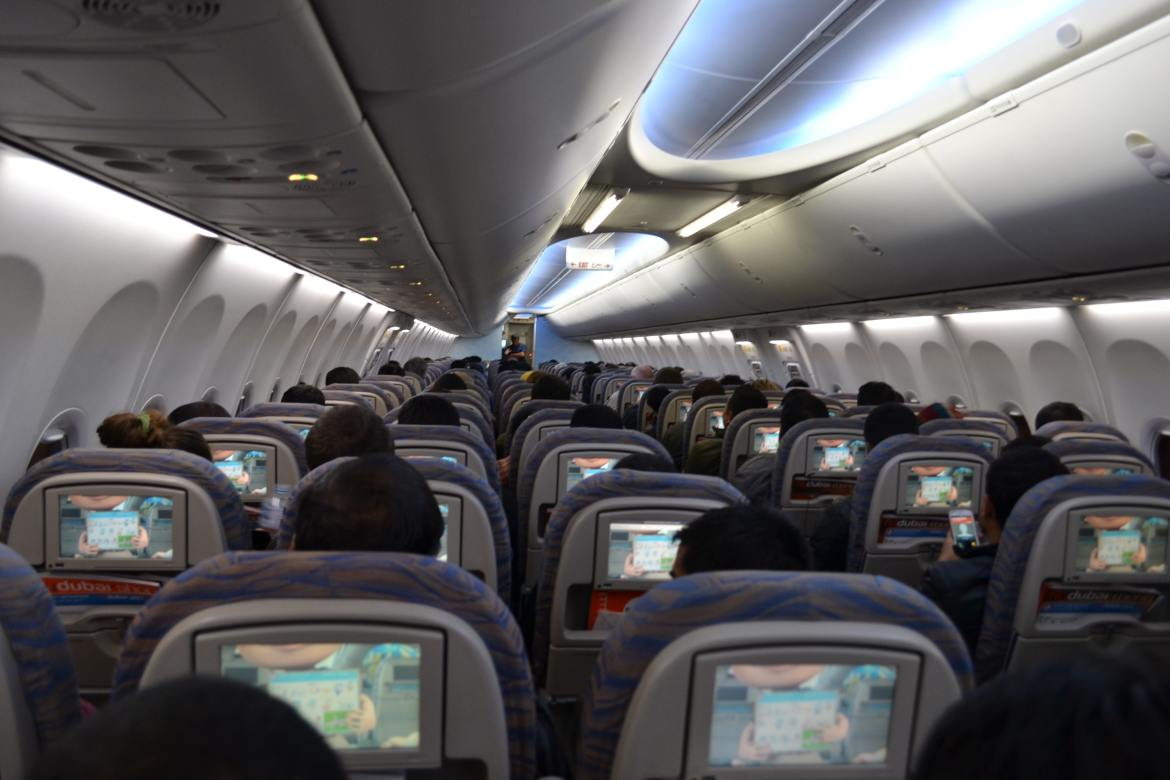 Inside of an airplane with multiple passengers watching screens