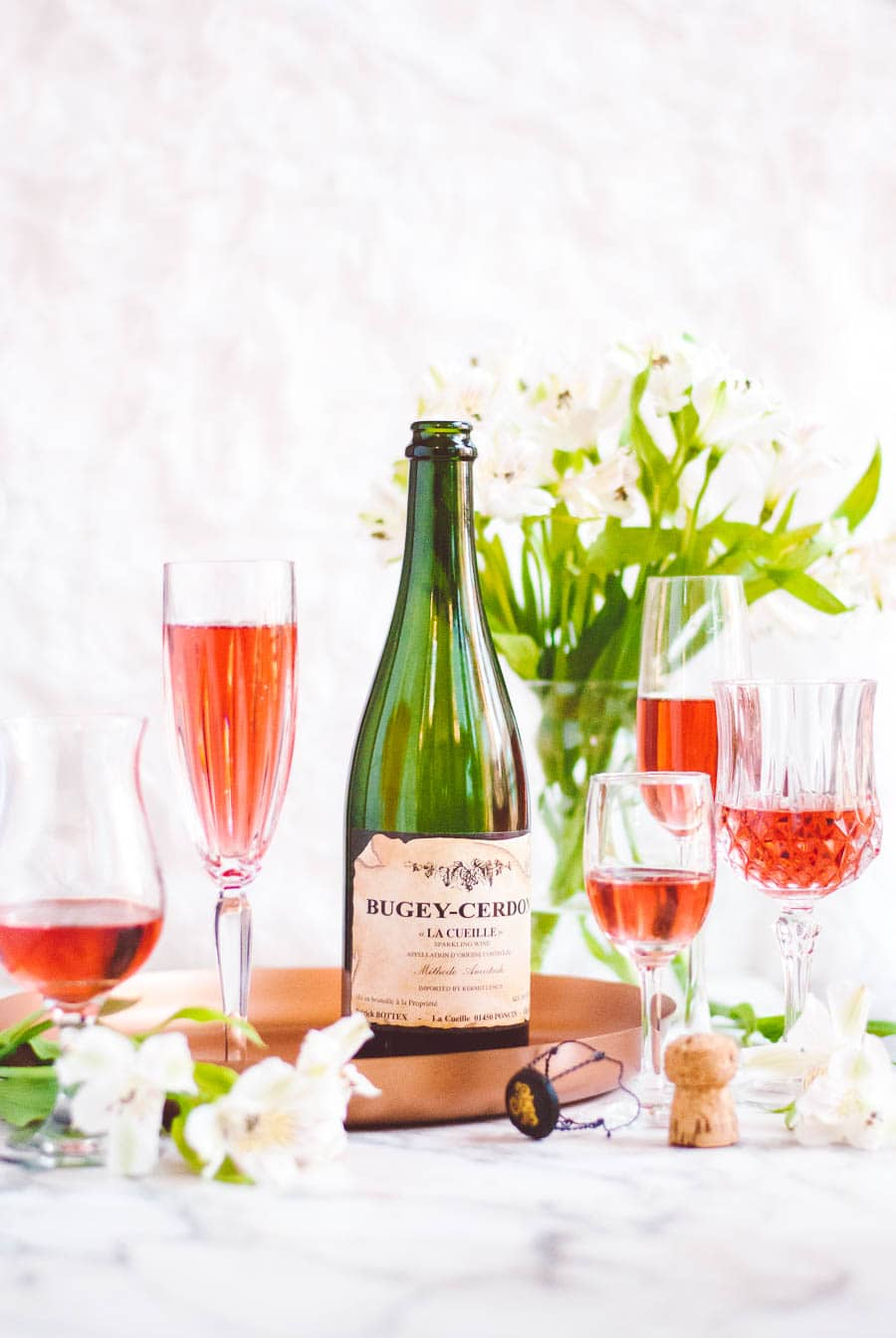 bottle of Bugey-Cerdon La Cueille French sparkling wine with filled wine glasses and flowers