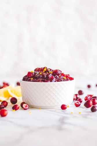 A white cup holding Cranberry Sauce with Grand Marnier and cranberries scattered around