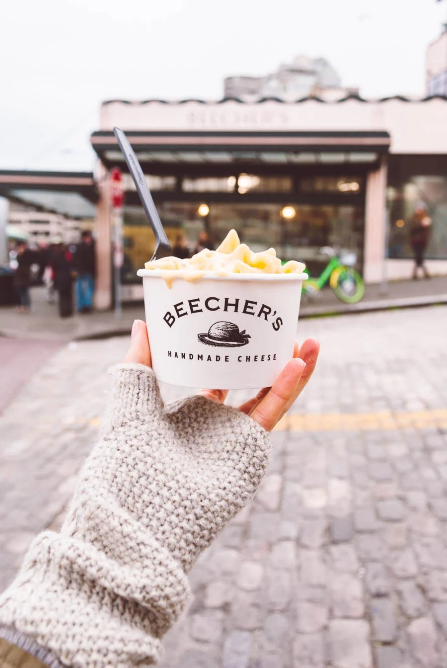 Hand holding a white cup of Beecher's mac and cheese in front of their Seattle location store front