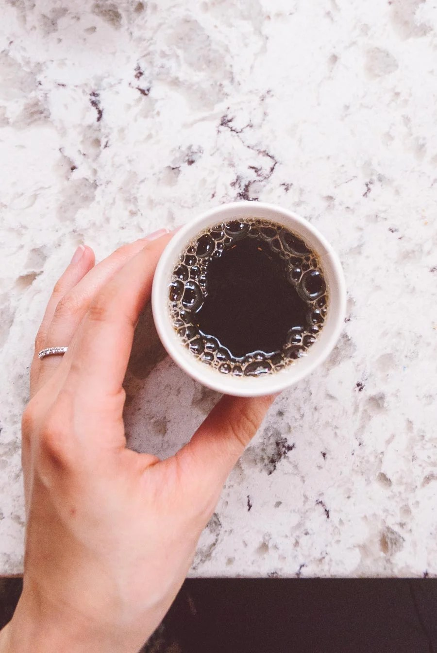 Overhead shot of a cup of coffee on a white marble table with a hand holding the cup.