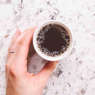 Hand holding a cup of coffee on a white table.