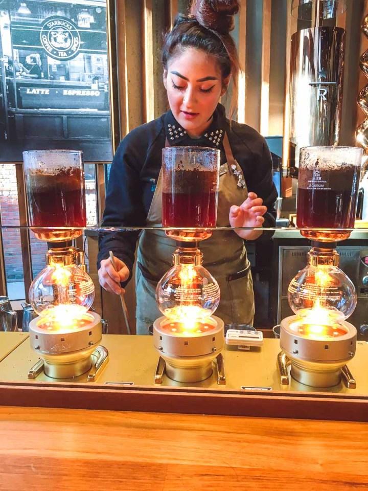 Starbucks Experience Bar barista brewing three siphon coffee machines
