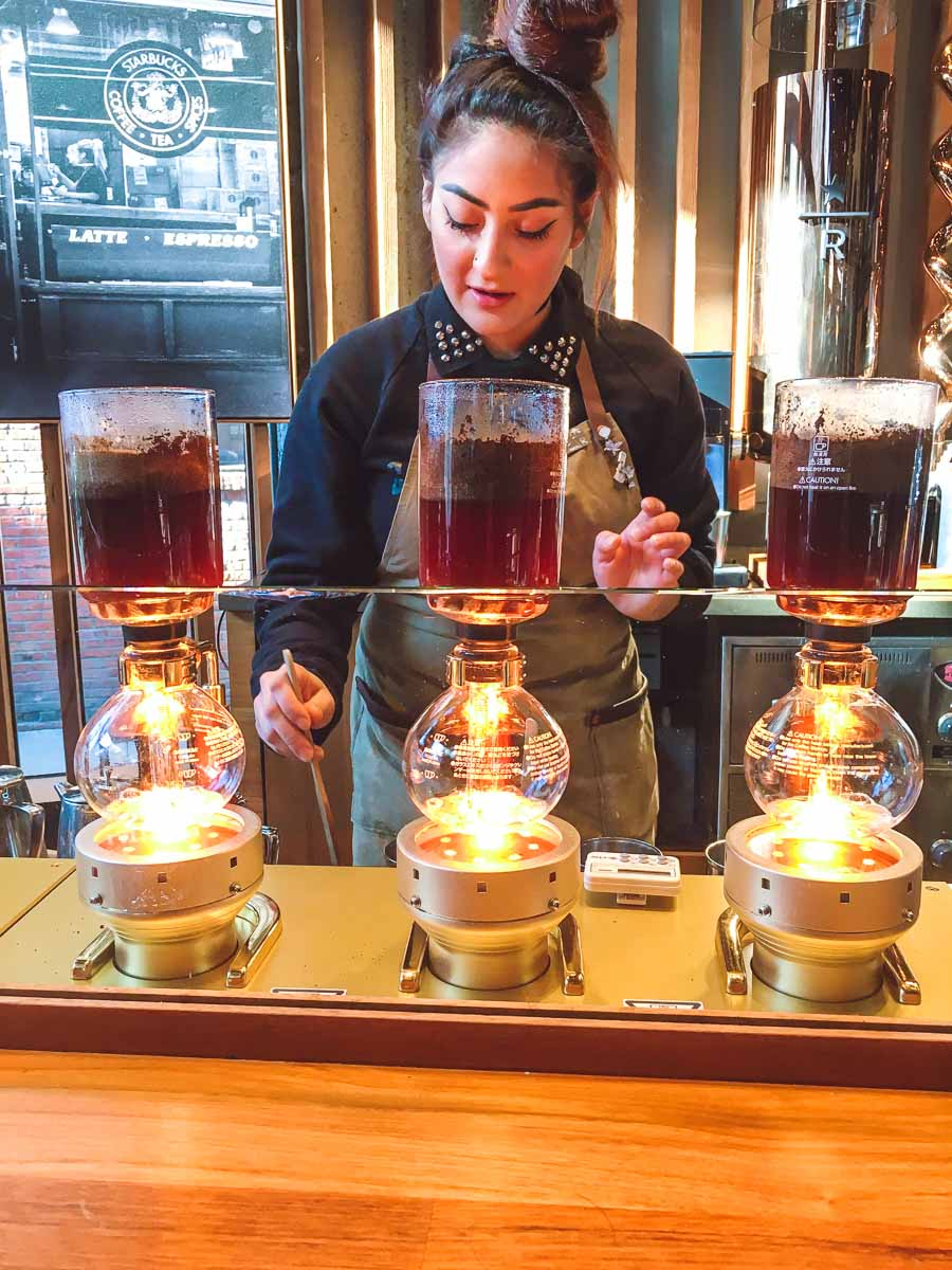 Starbucks Experience Bar barista brewing three siphon coffee machines