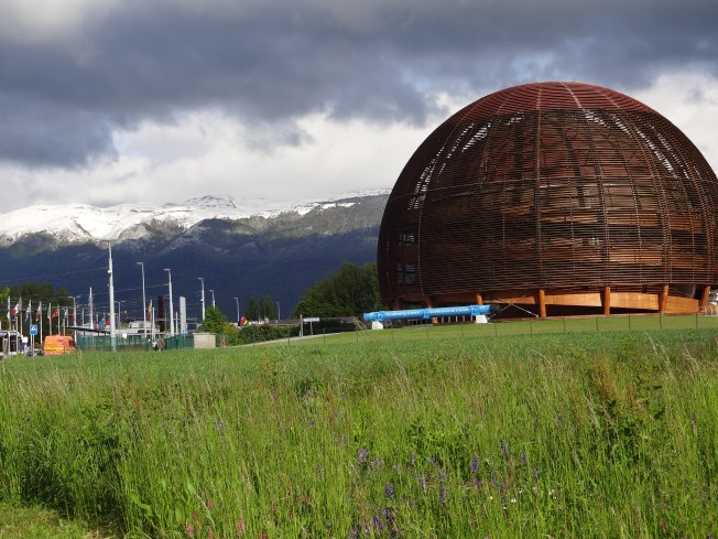 The CERN globe (Geneva, Switzerland), spring flowers in the front, snowy Jura range in the background - 24 May Photo: PK Read