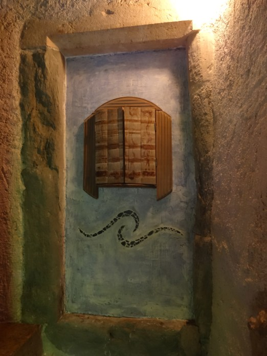 A stone door in our tower, with an installation we put in. The stripes on the wood doors are from the metal bands, the frame of the piece is from the bottom of the old wash barrel. Photo: PK Read