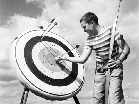 h-lefebvre-1960s-boy-jeans-striped-t-shirt-holding-bow-and-pulling-arrow-out-of-target-bull-s-eye