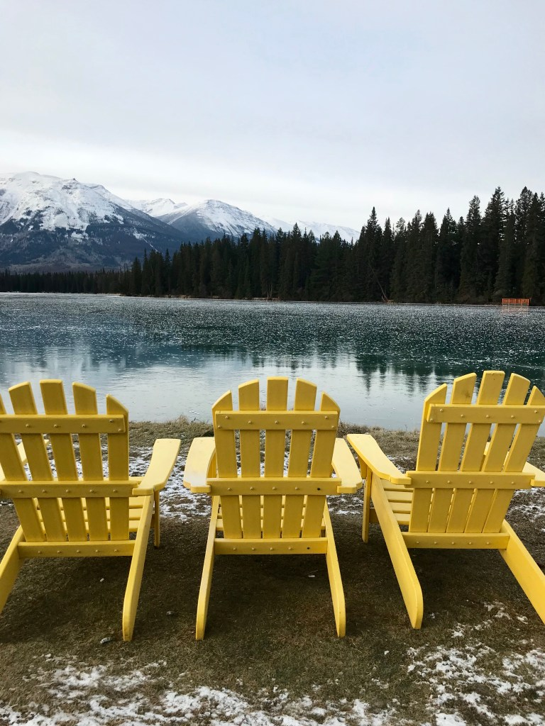 A stunning view of yellow chairs at Lake Beauvert while attending Christmas in November at Fairmont Jasper Park Lodge