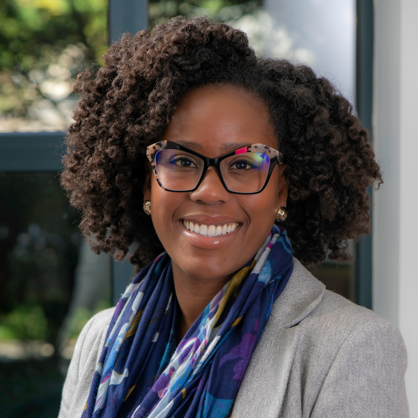 Adia Gooden, a Black woman with curly dark hair, glasses, and scarf