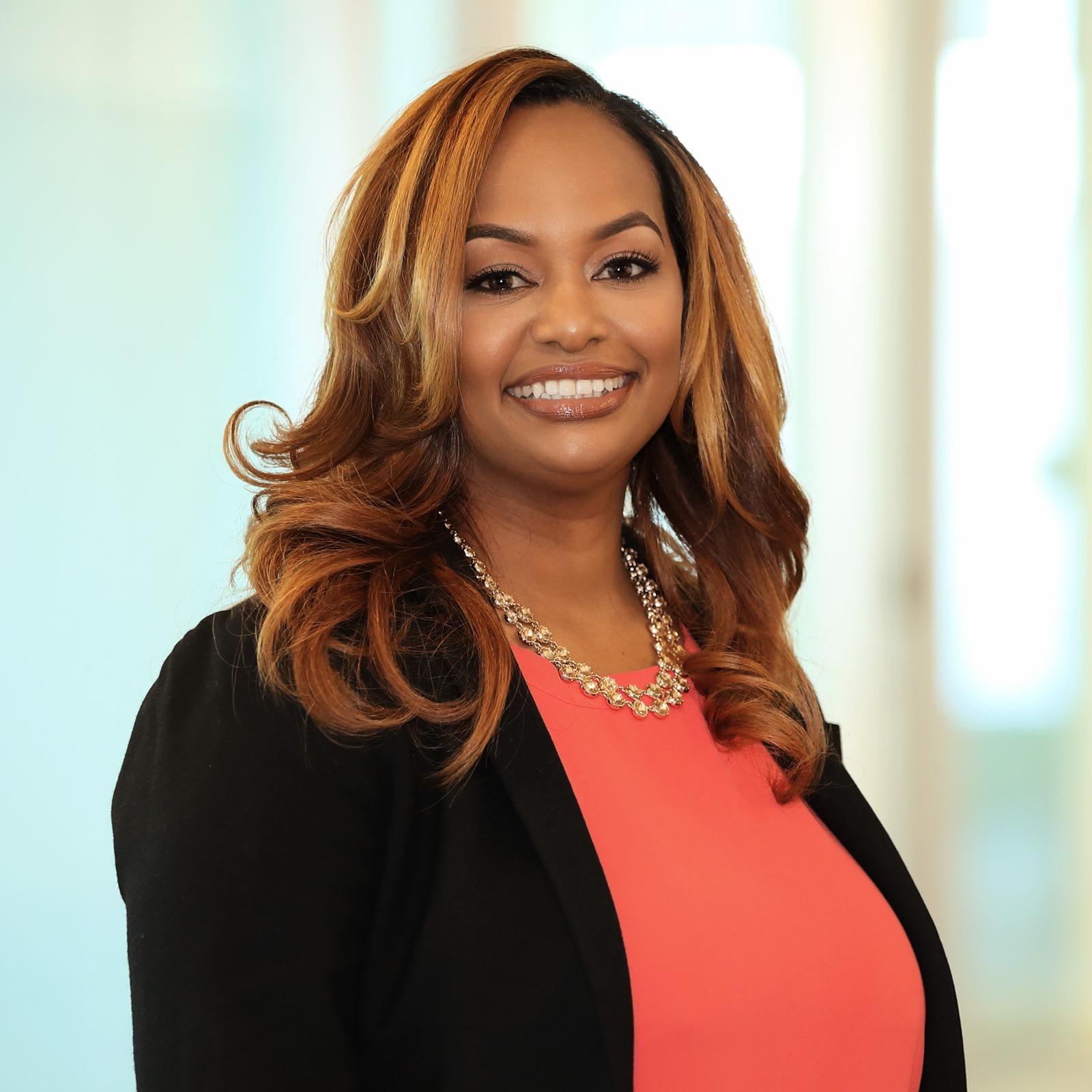 Sharawn Connors, a Black woman with medium auburn hair, orange blouse, and black jacket