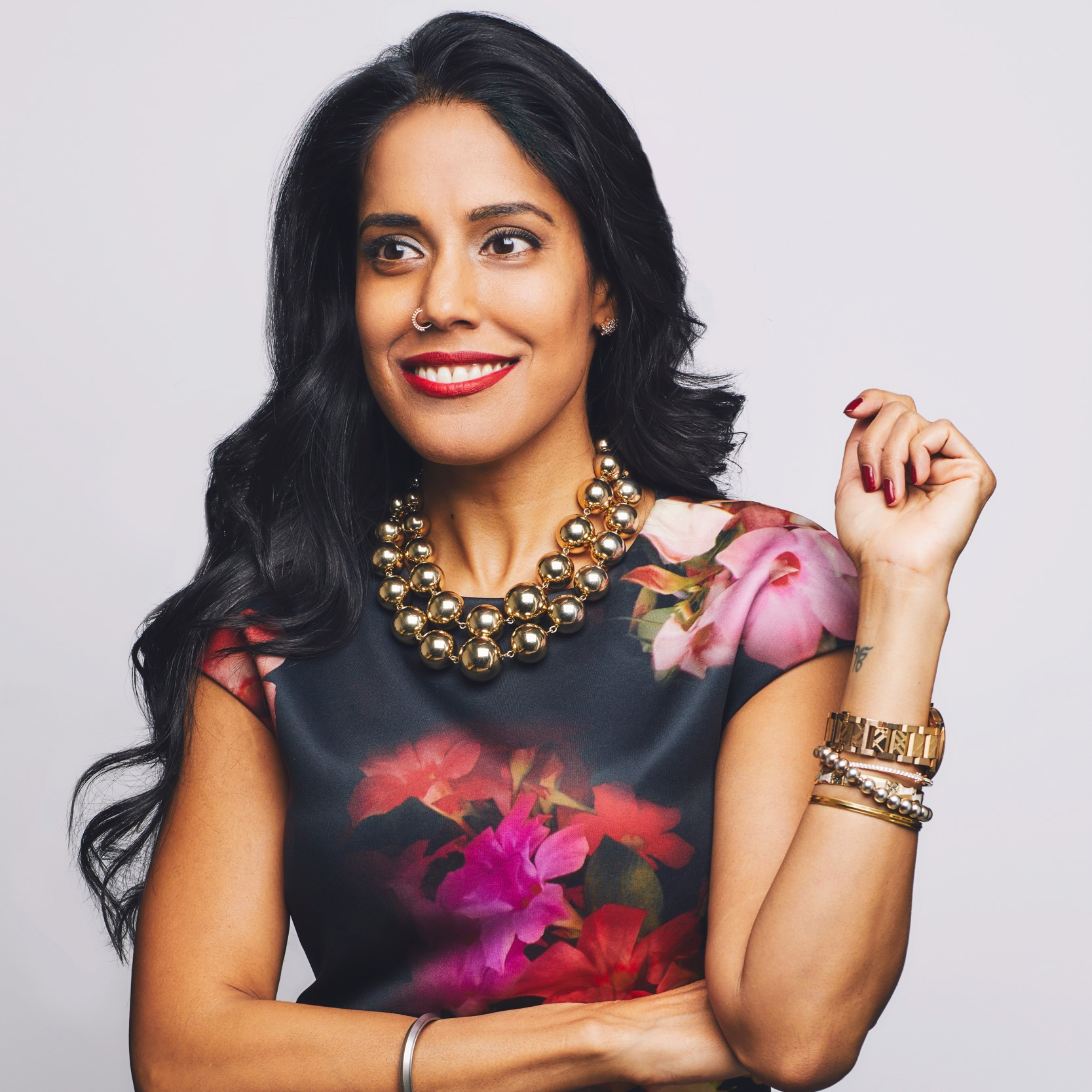 Headshot of Ritu Bhasin, a Punjabi Indian-Canadian woman with long, wavy black hair and a navy and pink floral dress