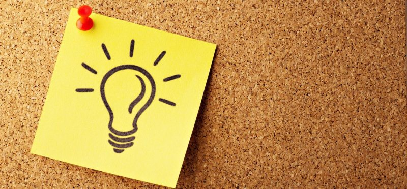sticky note with a drawing of a lightbulb, pinned to a corkboard