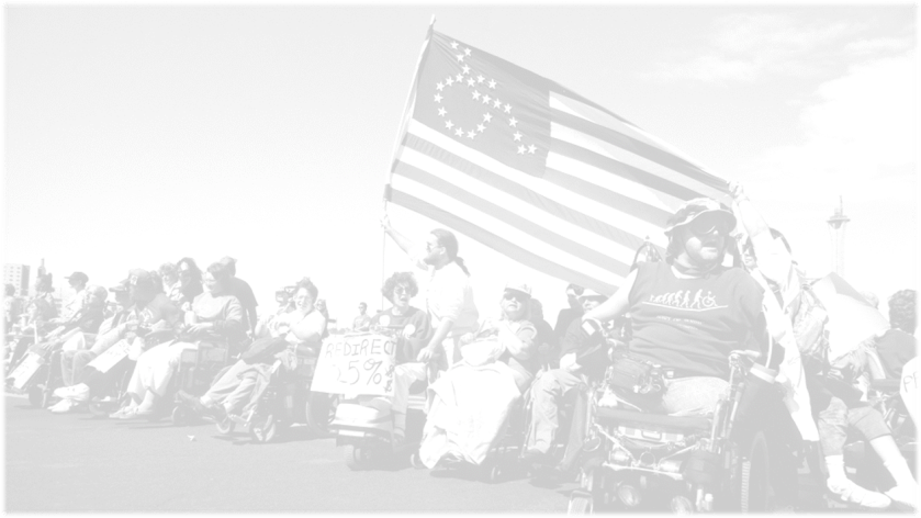 black and white phot of wheelchair users from ADAPT advancing across a field with an American flag, the stars in the form of a wheelchair logo