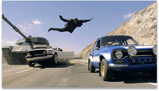 Movie stunt of an actor leaping from one car to another in mid air. There is a tank crushing the car he is leaping from