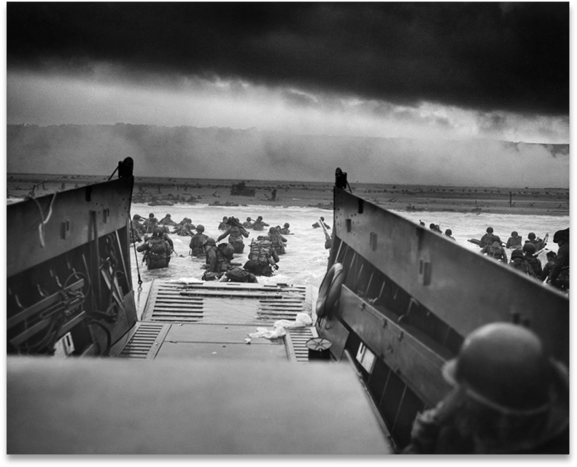 Black and white picture of troops landing at Normandy moving out of a landing craft toward the beach.