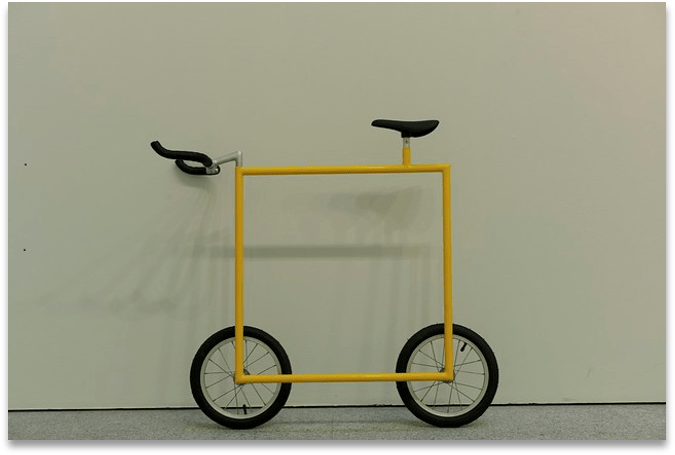 Strange yellow and black bicycle with a perfectly square frame and no brakes.