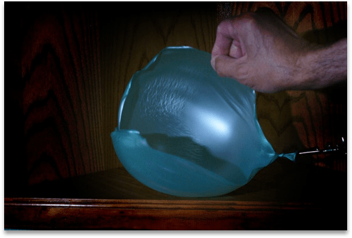 a balloon being pricked by a person's hand and collapsing