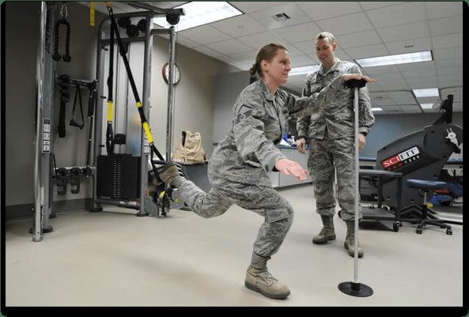 A female soldier doing orthopedic rehabilitation under PT supervision.