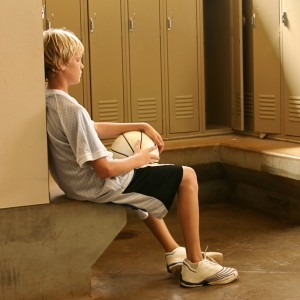 sad basketball kid in locker room cropped