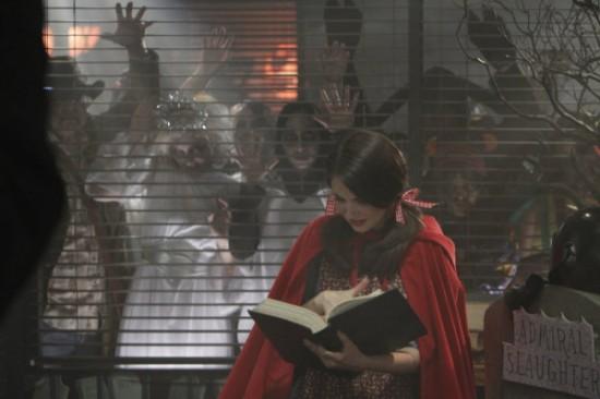 une jeune fille en costume du petit chaperon rouge cherche une solution dans un livre pendant que les zombies grattent à la vitre