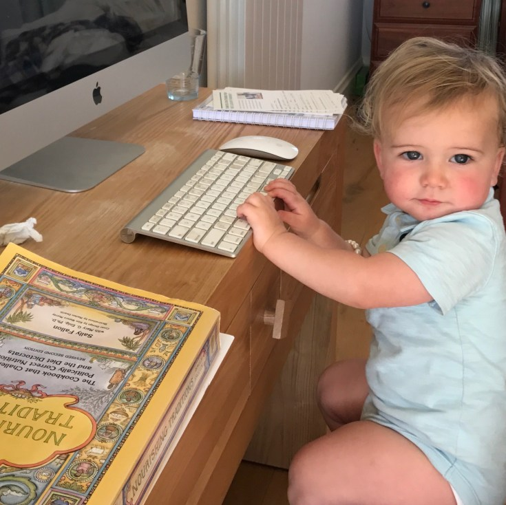 Fintan sitting at the computer with Sally Fallon's Nurishing Traditions book