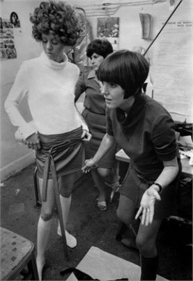 21 Oct 1967 --- Fashion designer Mary Quant adjusts a miniskirt on a fashion model. --- Image by © Bettmann/CORBIS