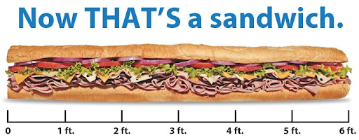 text: Now THAT'S a sandwich. Picture of a 6 foot long submarine sandwich.