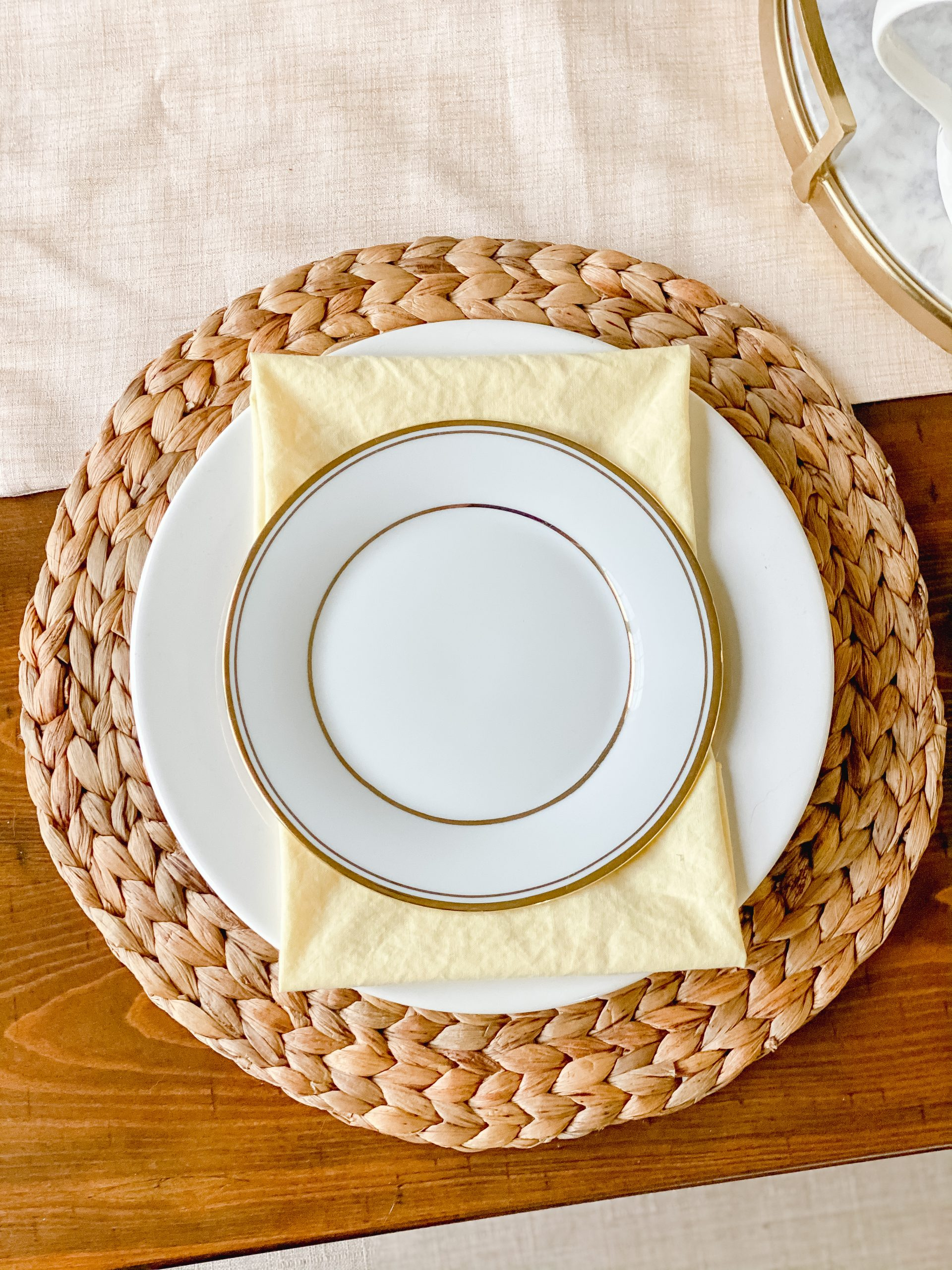 Table decor for spring with yellow napkins and gold rimmed plates in the place setting.