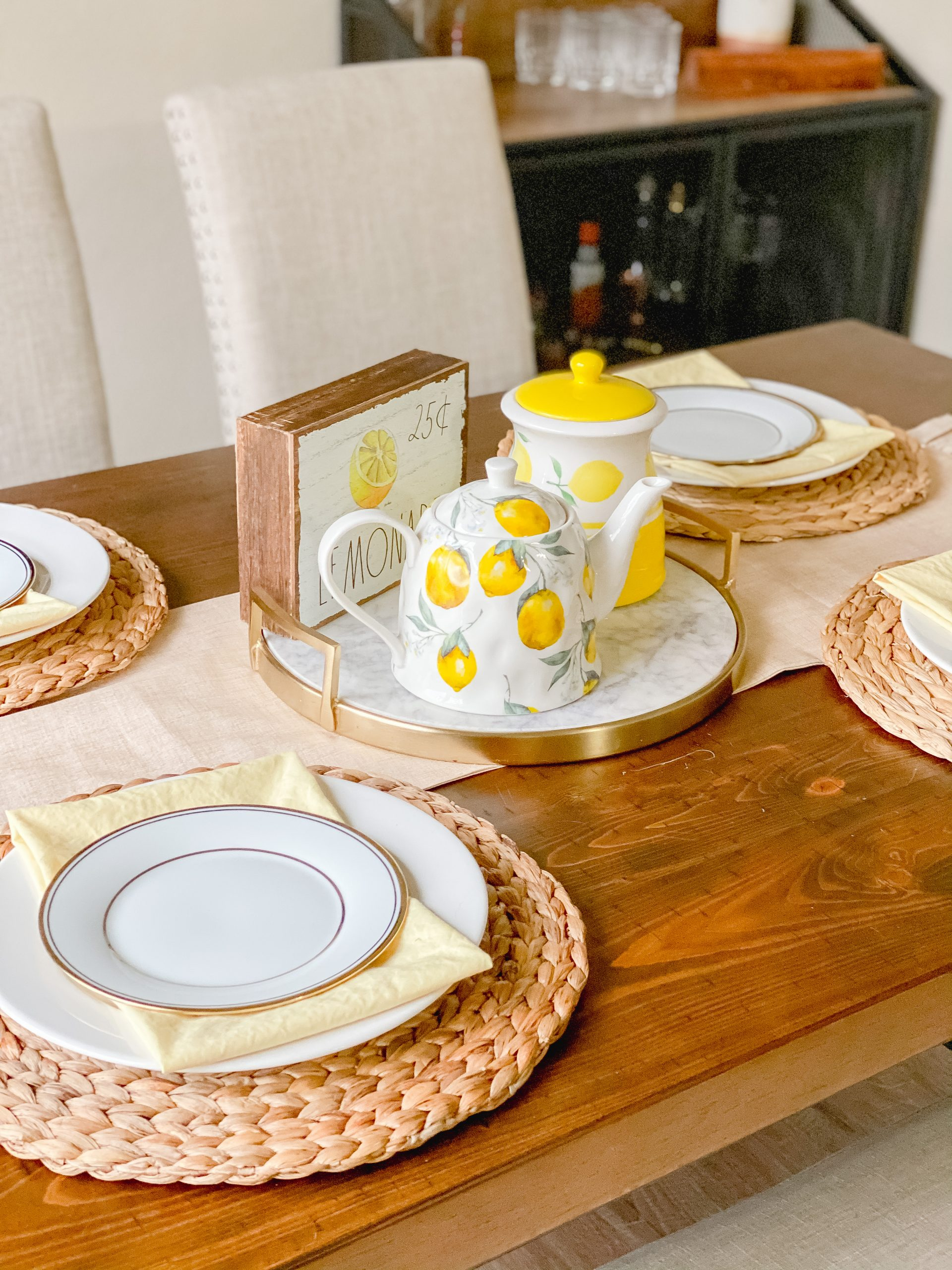 Table decor for spring with yellow napkins and lemon decor.