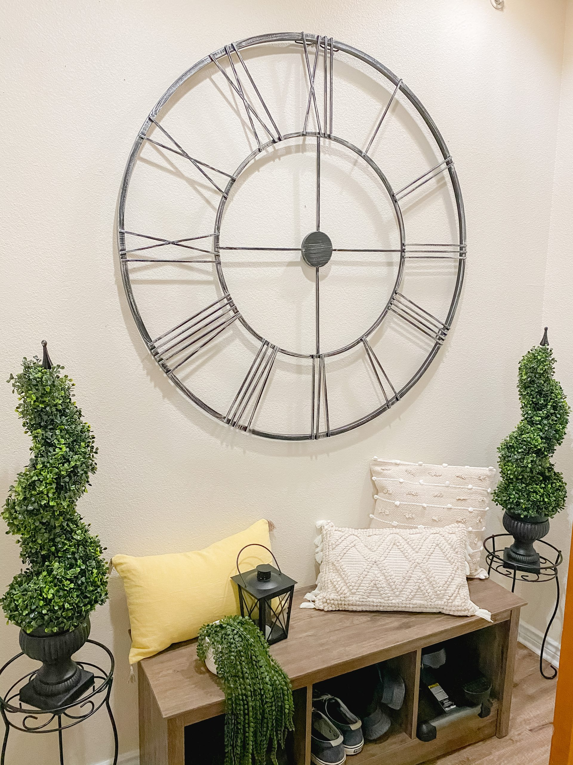 Spring decor in the entry way with an iron clock and greenery.