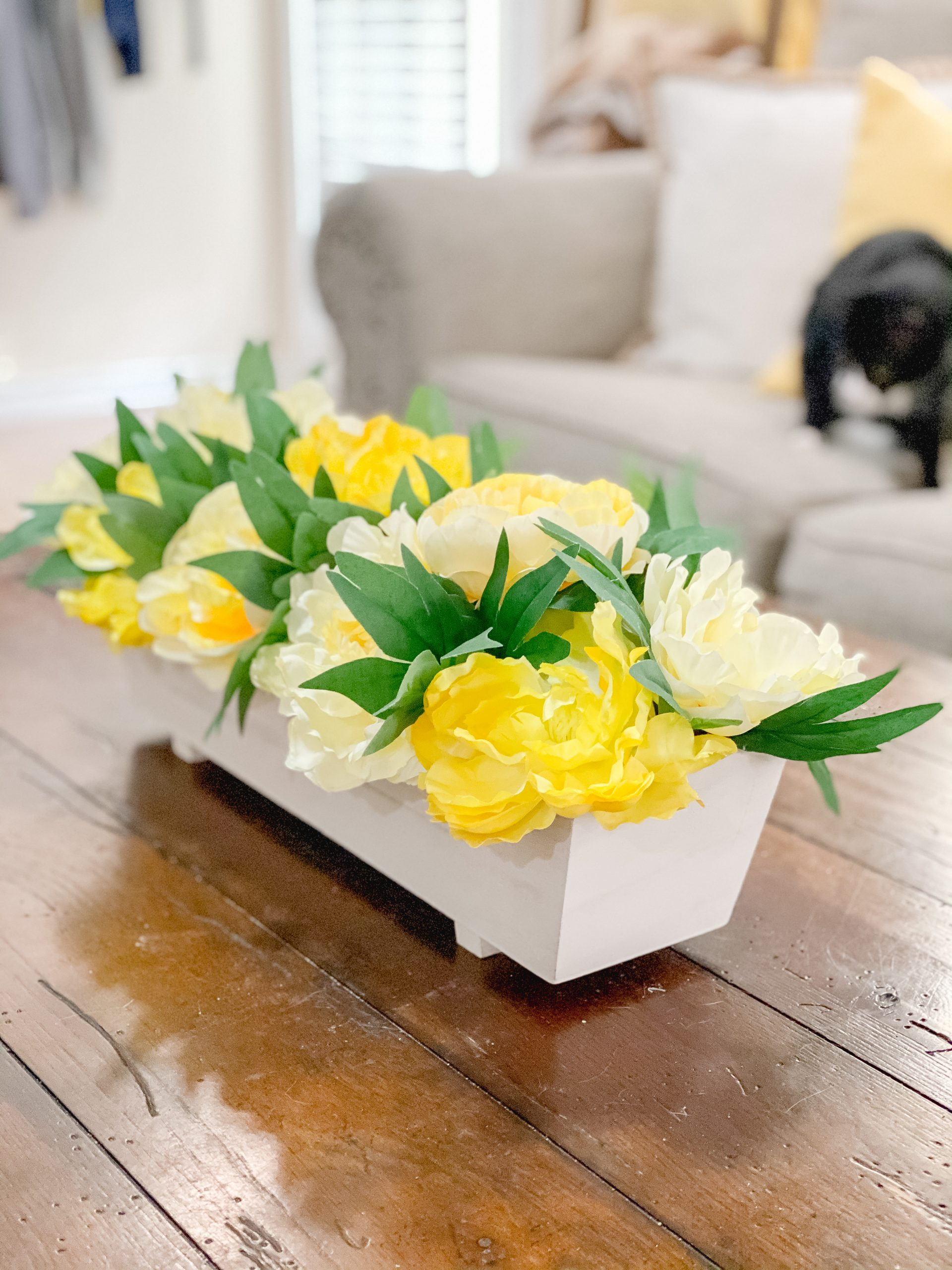 Spring decor on coffee table with spring planter box and yellow flowers.