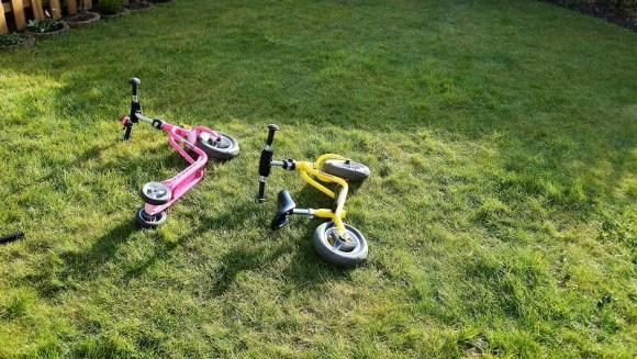 Laufrad und Roller im Garten