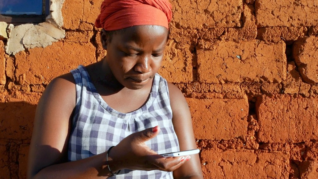 African-stock-video-of-a-black-rural-woman-texting-on-her-cell-phone-2