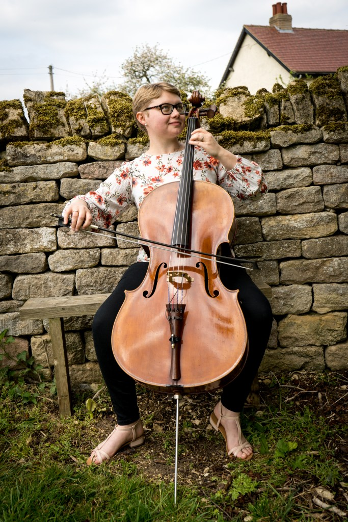 Sarah James, Cellist in the Chapel Hill Duo playing her cello on a bench in front of a drystone wall covered in moss with a cottage in the background.