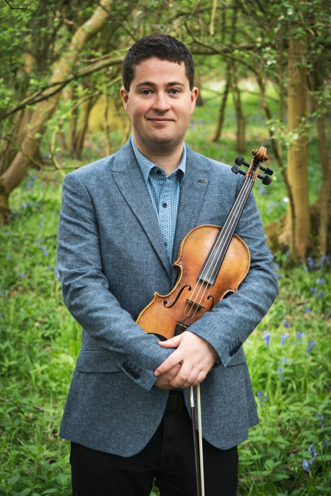 Violinist for the Chapel Hill Duo, Jaya Hanley. Headshot in bluebell forest, wearing blue herringbone blazer and holding violin.