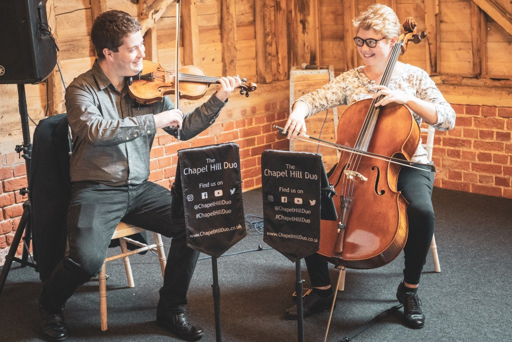 The Chapel Hill Duo perform their violin and cello song covers at Childerley Long Barn.