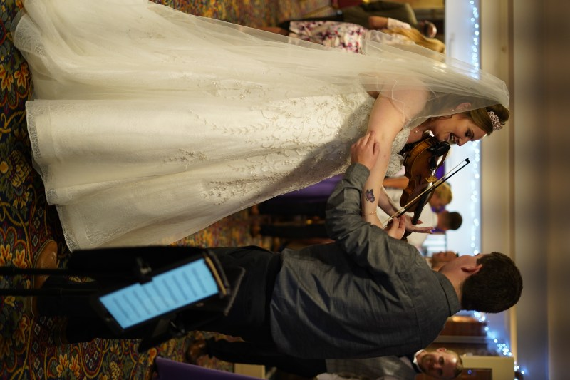Violinist jaya hanley giving a violin lesson to a bride on her wedding day. Full length dress shot.