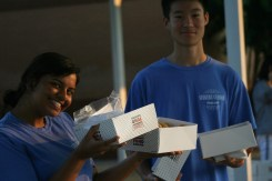 Student Council Representatives Anushka Koratana (11) and Samuel Xie (11) hand out donuts under the bus canopy.