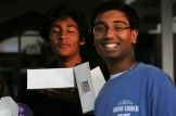 Student Council Representatives Kamal Korrapati (10) and Hrishi Mungala (11) hand out donuts under the bus canopy.
