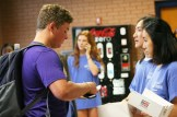 Student Council Representative Youngho Lim (12) hands out a donut to John Irwin (11) by the Senior Parking Lot entrance.