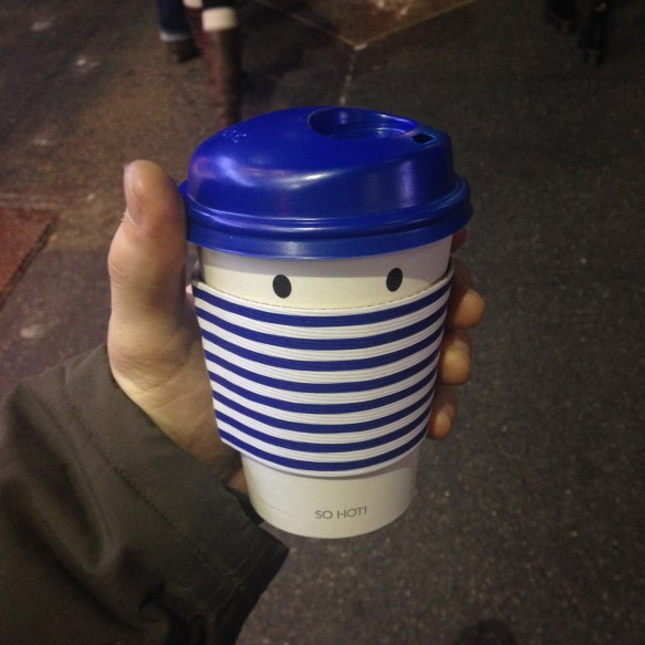 A coffee cup, wearing stripes and a beret.