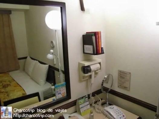 Justo del lado derecho de la cama tienes una pequeña mesita y después esta un escritorio con un gran espejo. Como pueden ver esta ahí el secador de pelo y varios libros que la verdad no recuerdo de que eran XD