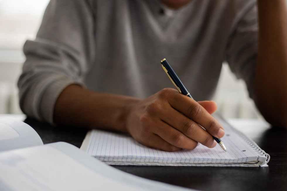 crop black man writing in copybook