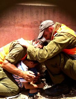 IDF officers shield a 4-year-old boy, protecting him with their own bodies during a Hamas rocket attack, during Operation Protective Edge, 15/7/14.