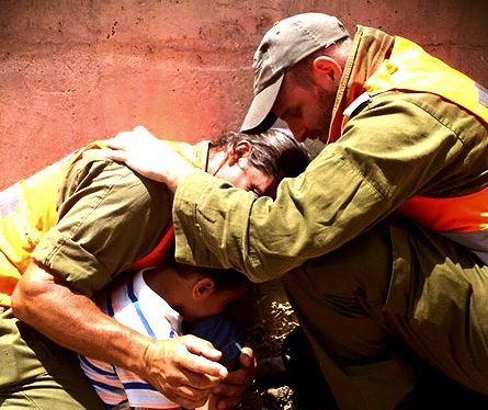 Detail: IDF officers shield a 4-year-old boy, protecting him with their own bodies during a Hamas rocket attack, during Operation Protective Edge, 15/7/14.