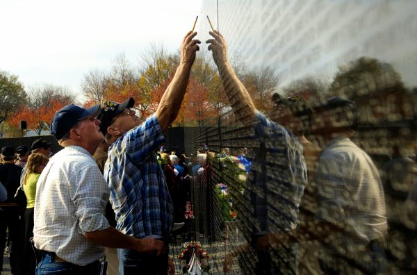 U.S. veterans point out a familiar name at the Vietnam War memorial following a Veterans Day ceremony, Nov. 11, 2006.