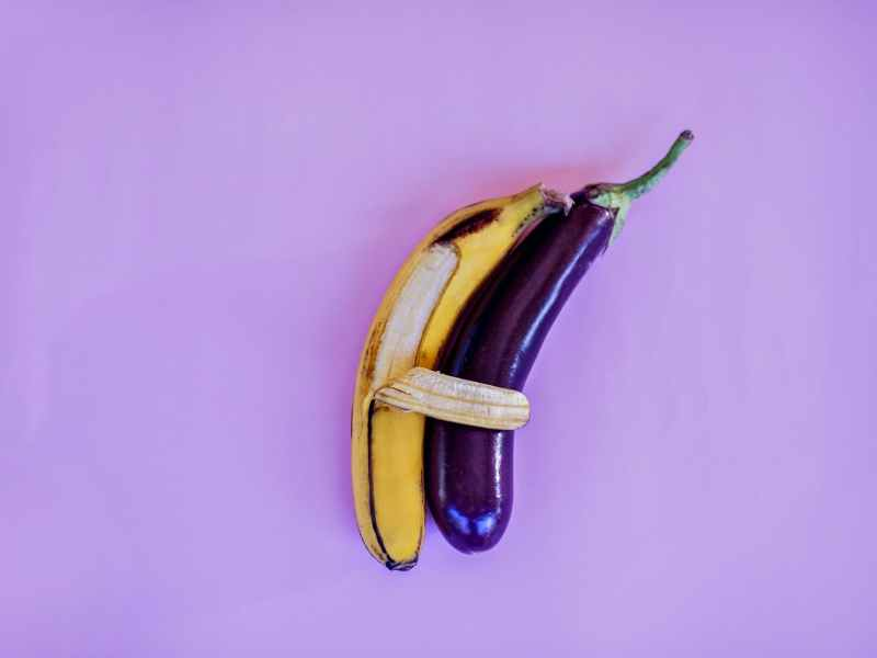 banana and eggplant on violet surface