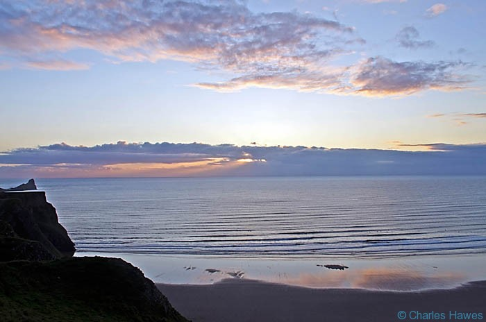 Sunset over Rhossili Bay from the Wales Coast Path at Rhossili photographed by Charles Hawes. Walking in Wales.