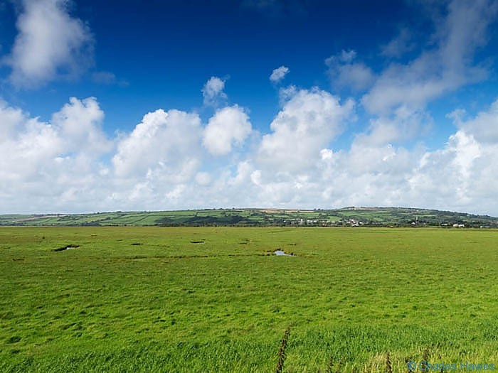 View across the marshes near Kidwelly photographed on The Wales Coast path between Llanelli and Kidwelly by Charles Hawes. Walking in Wales.